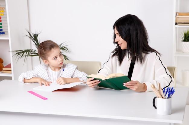 Matka i córka siedzi przy stole i razem odrabiają lekcje w domu.