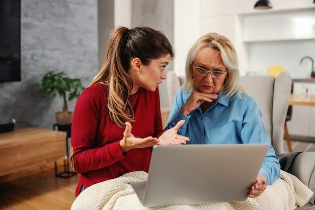 Matka i córka siedzi razem w domu i za pomocą laptopa