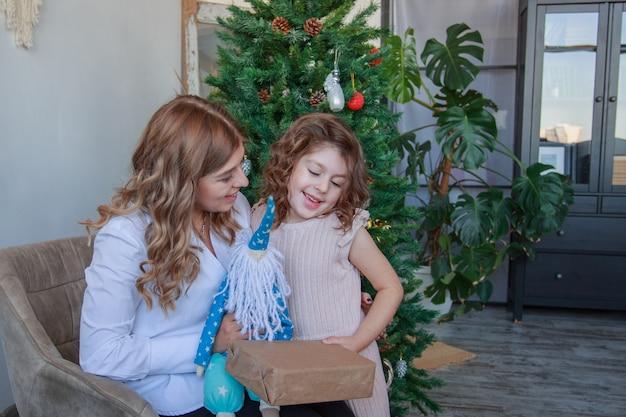 Matka i córka siedzi w pobliżu choinki z prezentem i zabawką mikołaja.
