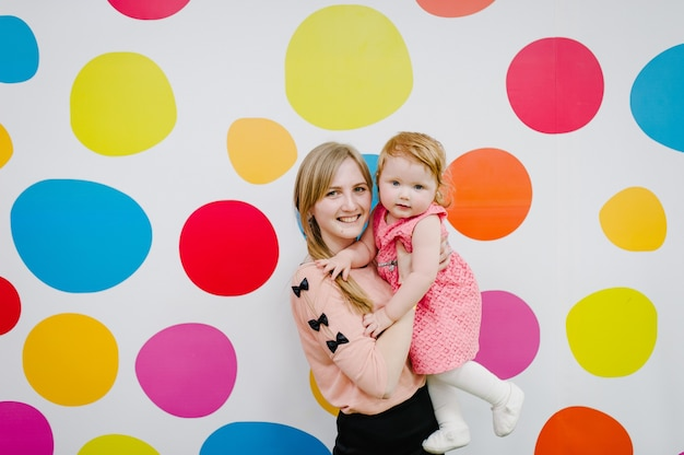 Matka i córka, śmiejąc się i szczęśliwi, stoją na kolorowym tle. pojęcie radości. szczęśliwa rodzina, dziewczyny w pobliżu kolorowe tło.