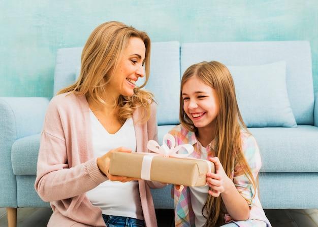 Matka i córka śmiejąc się i trzymając pudełko
