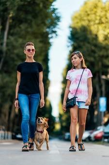 Matka i córka spaceru na ulicy z psem