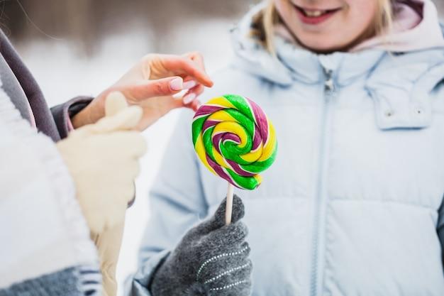Matka i córka spacery po lesie zimą, owinięte w koc, lollipop, lollipop na patyku