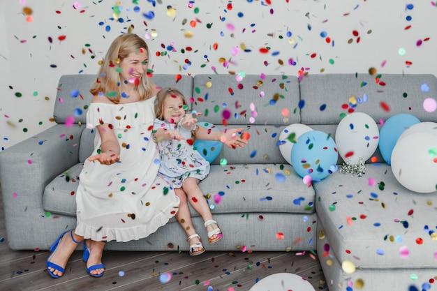 Matka i córka świętują urodziny balonami i konfetti.