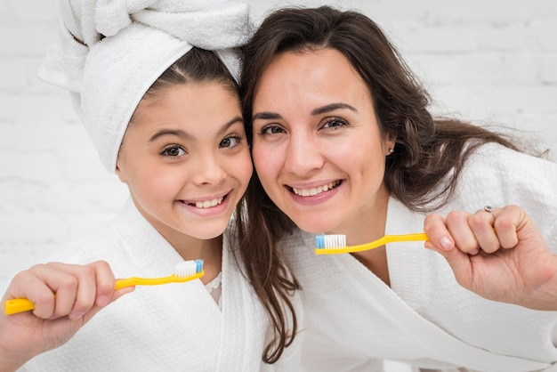 Matka i córka szczotkuje ich zęby z bliska