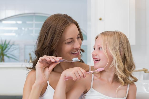 Matka i córka szczotkuje zęby w łazience
