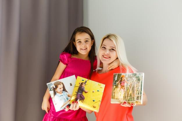 Matka i córka trzymają płótno fotograficzne w domu