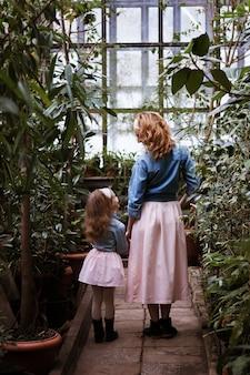 Matka i córka trzymają się za ręce i stoją plecami. mała dziewczynka trzymać rękę matki. stań na małej drodze w lesie lub parku. pokaż się z powrotem. światło dzienne. noś te same sukienki. zabawny wygląd