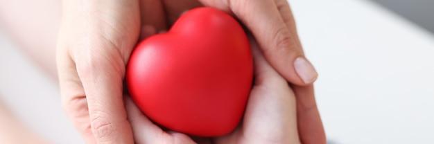 Matka i córka trzymają zbliżenie serca czerwonej zabawki