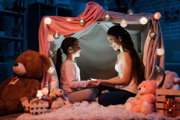 Matka i córka trzymając latarkę ręce.
