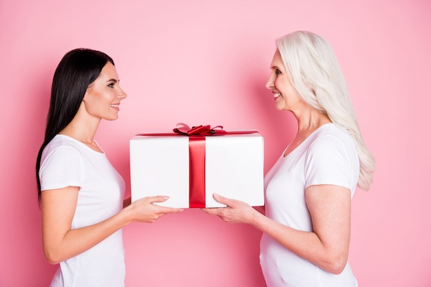 Matka i córka trzymając prezent na różowym tle