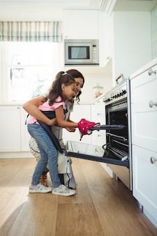 Matka i córka umieszcza tacę ciastka w piekarniku
