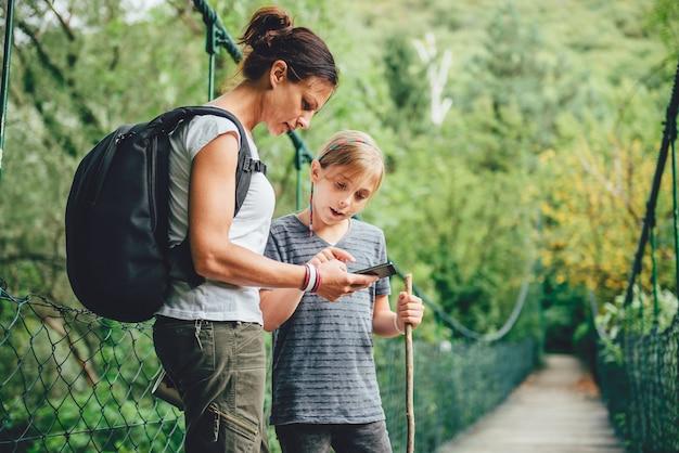 Matka i córka używa mądrze telefon na drewnianym moscie