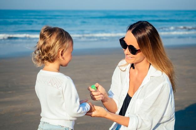 Matka i córka używają na plaży środka antyseptycznego