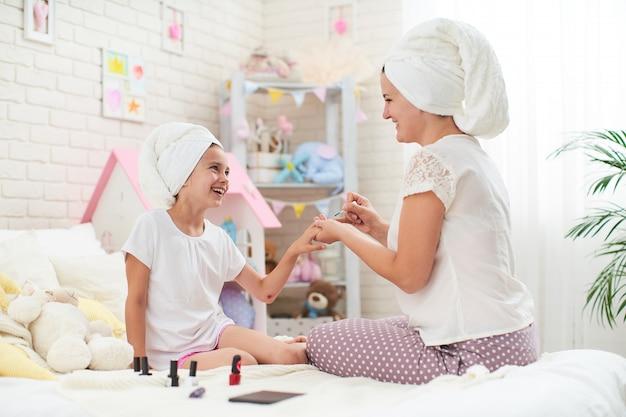 Matka i córka w domowych ubraniach i ręcznikach na głowie robią manicure