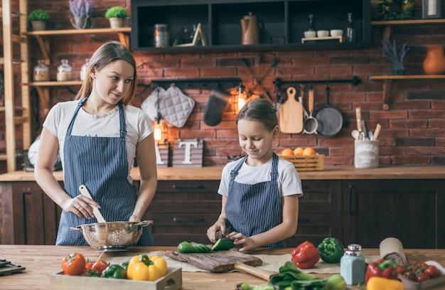 Matka i córka w fartuchach gotować