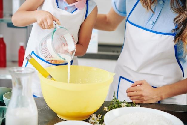 Matka i córka w fartuchu, wlewając ciepłe mleko do miski podczas robienia ciasta na ciasteczka