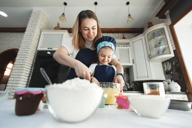 Matka i córka w identycznych fartuchach i czapkach szefa kuchni gotują w kuchni. mieszają ciasto drewnianą szpatułką, uśmiechają się i patrzą w kamerę.