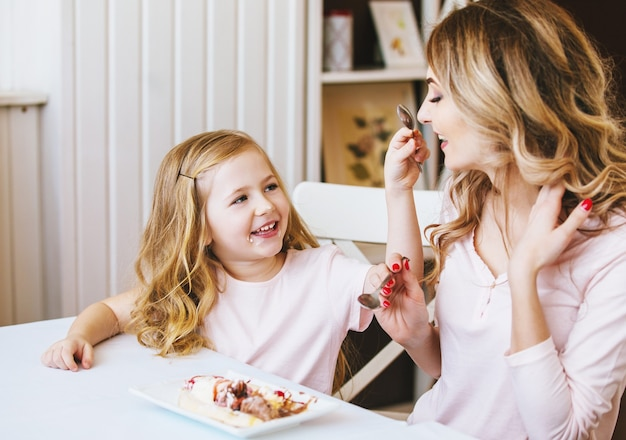 Matka i córka w kawiarni siedząc przy stole i karmią się lodami