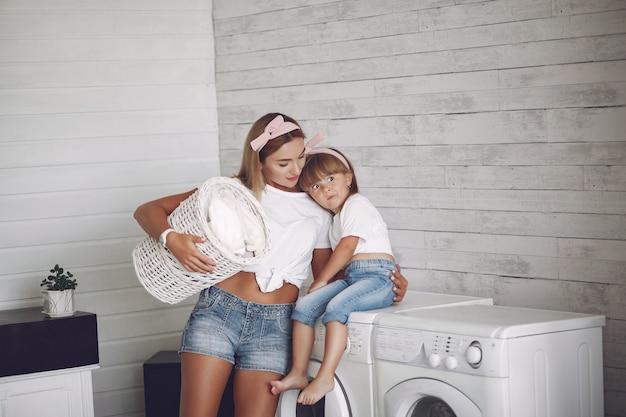 Matka i córka w łazience w pobliżu mycia maszyny