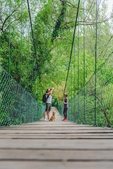 Matka i córka w lesie spacery nad drewnianym mostem