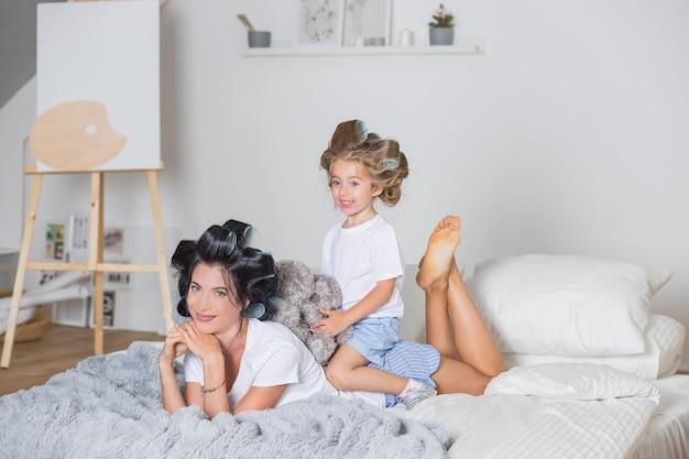 Matka i córka w lokówki do włosów. szczęśliwa mama i córka bawią się na łóżku w piżamie. szczęśliwa kochająca rodzina