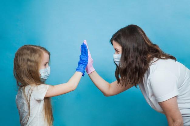 Matka i córka w masce i rękawiczkach dają piątkę