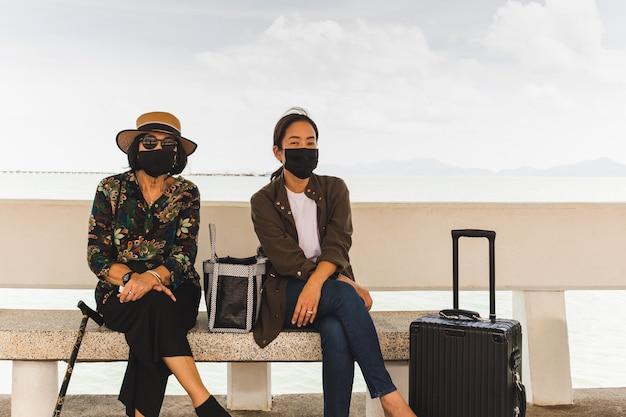 Matka i córka w ochronnych maskach na przystani z bagażem.