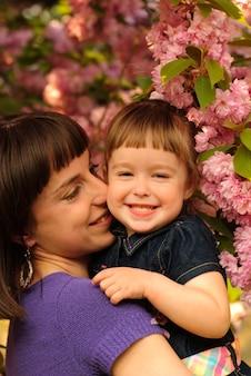 Matka i córka w ogrodzie, pod drzewem sakura. wiosna.