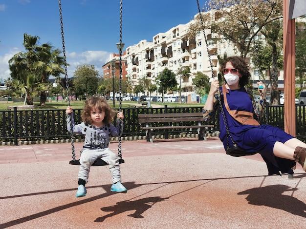 Matka i córka w parku bawią się na huśtawce