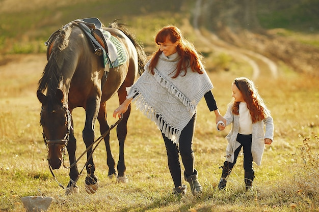 Matka i córka w polu bawić się z koniem