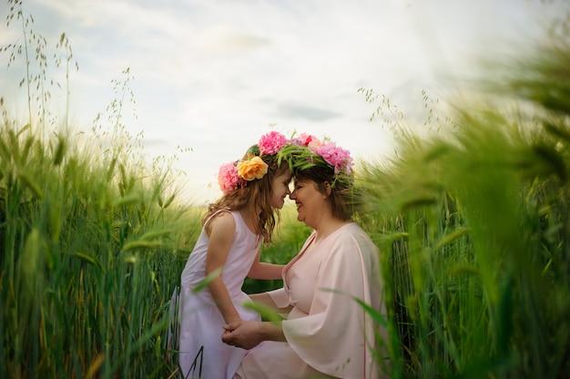 Matka i córka w różowych sukienkach w zielonym polu pszenicy. na głowach mają wianki z kwiatów.