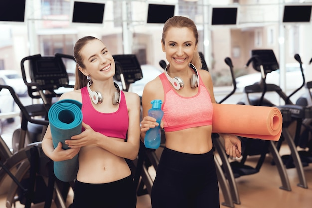 Matka i córka w sportswear z matami stoi przy gym