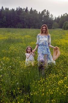 Matka i córka w sukienkach i kapeluszu stoją w polu żółtych kwiatów w letni dzień