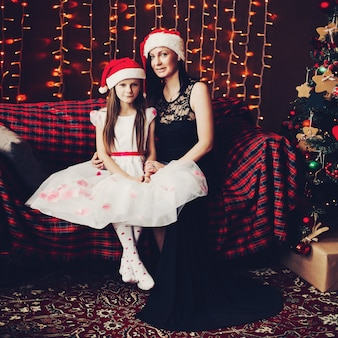 Matka i córka w święty mikołaj kapeluszu przeciw oświetleniowej girlandzie.