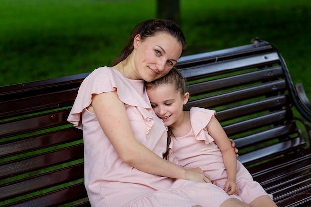 Matka i córka w tych samych ubraniach siedzą na ławce w parku latem