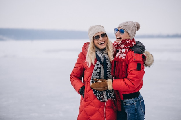 Matka i córka wpólnie chodzi w parku w zimie