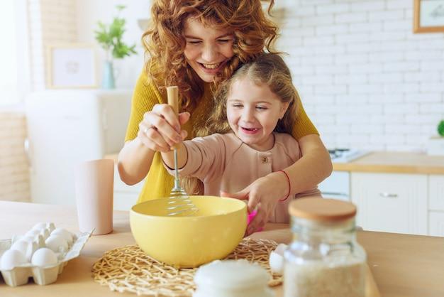 Matka i córka wspólnie przygotowują ciasto w kuchni