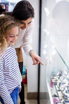 Matka i córka wybiera zegarek na rękę z wystawy sklepowej