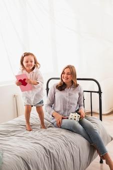 Matka i córka z kartka z pozdrowieniami na łóżku