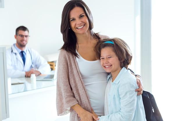 Matka i córka z samiec lekarką patrzeje kamerę w biurze.