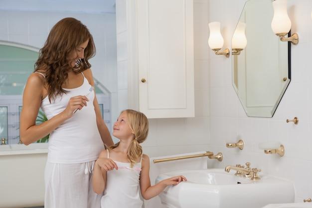 Matka i córka z szczoteczki do zębów w łazience umywalka