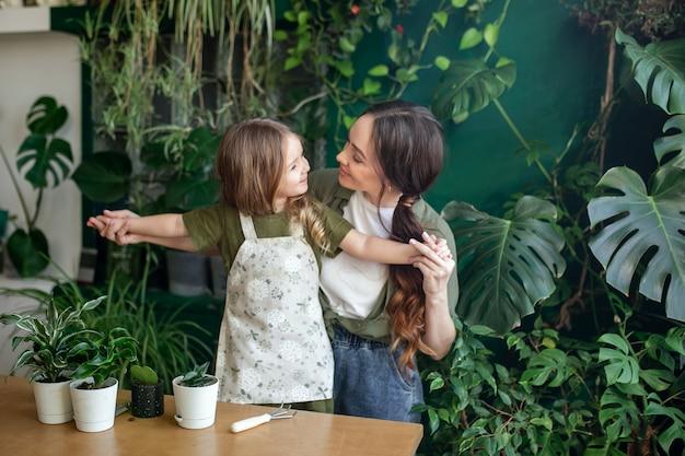 Matka i córka zasadzamy zielone rośliny w szklarni