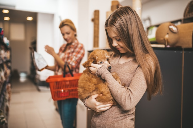 Matka i córka ze szczeniakiem pudla w sklepie zoologicznym.