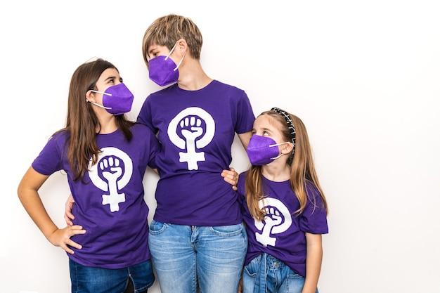 Matka i córki na białej ścianie, ubrane w fioletową koszulkę z symbolem pracujących kobiet w międzynarodowy dzień kobiet 8 marca, z maską na twarz na pandemię koronawirusa