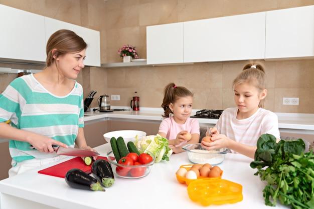 Matka i dwie córki gotuje w kuchni i ma zabawę, szczęśliwą rodzinę i samotną matkę