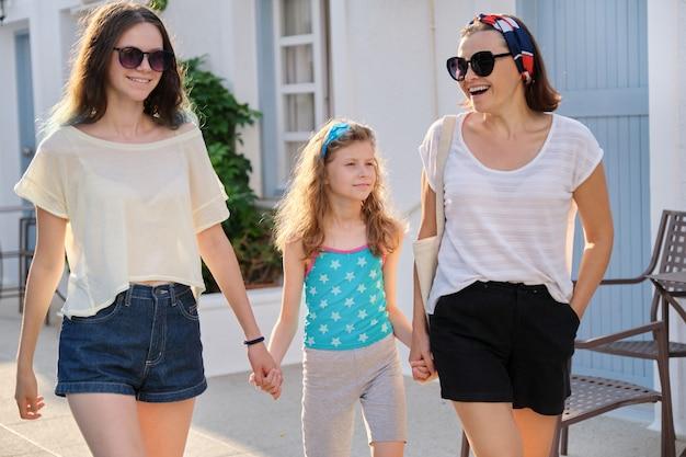 Matka i dwie córki nastolatka i najmłodsza idą razem trzymając się za ręce