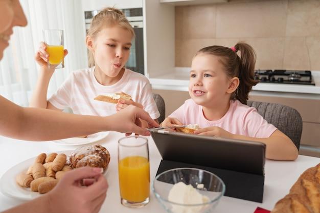 Matka i dwie córki po śniadaniu razem, szczęśliwa samotna matka koncepcja rodziny