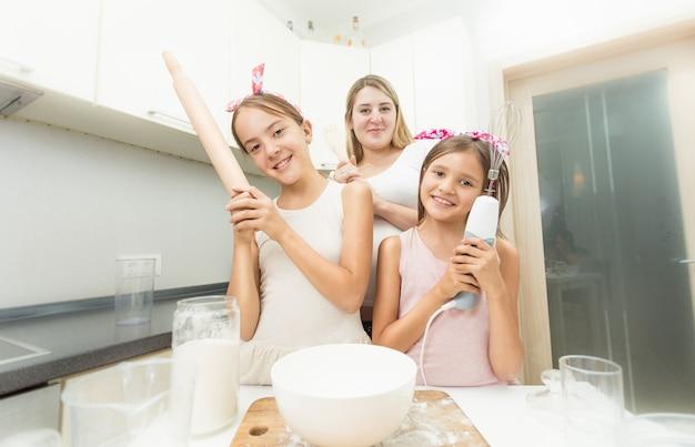 Matka i dwie córki pozują w kuchni podczas gotowania
