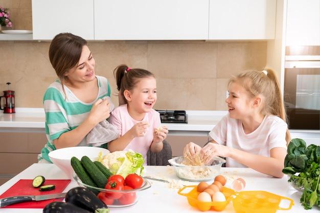 Matka i dwie córki robi ciasto w kuchni i ma zabawę, szczęśliwą rodzinę i samotną matkę